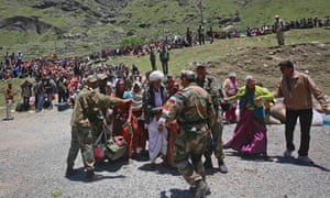 Soldiers stop survivors from going near an army helicopter as its lands during rescue operations at Badrinath, India. Early monsoon rains have swollen the Ganges, and swept away houses, killing at least 138 people and left tens of thousands stranded.