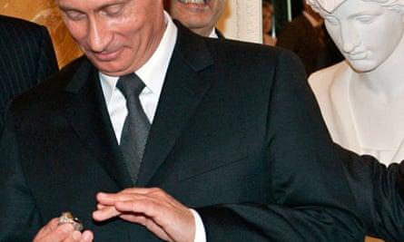 Vladimir Putin tries on a diamond-encrusted belonging to Robert Kraft