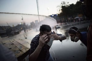 20 Photos: A protester reacts to tear gas fired by the riot police in Gezi Park
