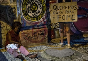 20 Photos: A demonstrator stands next to a homeless woman in Recife, Brazil