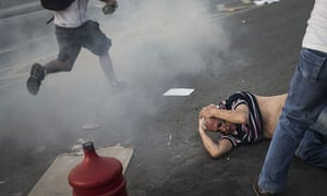 A man lies on the ground after police fired tear gas during a protest in Belo Horizonte