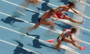 Athletes jumping hurdles