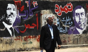A man walks past graffiti depicting Egyptian President Mohamed Morsi
