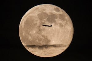 A silhouetted airplane flies past a super moon, the largest moon of the year, over New York.