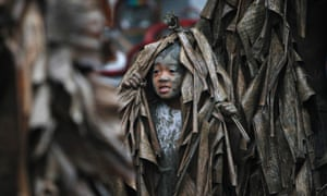 A boy, covered with mud and dried banana leaves, walks around the village to ask for candles before attending a mass celebrating the feast day of the Catholic patron Saint John the Baptist in the village of Bibiclat, Nueva Ecija, Philippines.