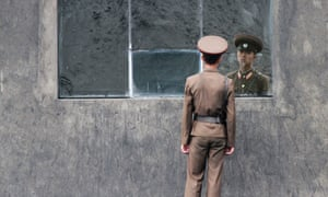 Mirror, mirror on the wall. A North Korean soldier stands in front of a window along the banks of Yalu River near the North Korean town of Sinuiju.