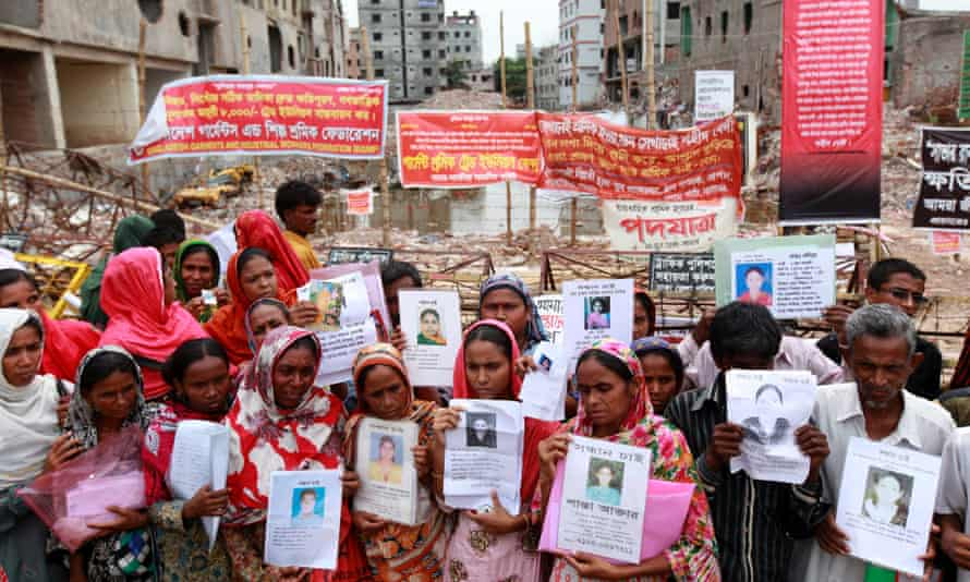 Relatives of the victims of the Rana Plaza building collapse attend a protest rally holding photos of the dead and missing workers.