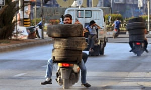 Men ride on mopeds as they transport tires towards a burning barricade in the northern city of Tripoli, Lebanon, during protests in support of Sunni Muslim Sheikh Ahmad al-Assir whose supporters have clashed with the Lebanese army in Sidon.