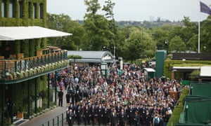 Tournament stewards escort the fans into the grounds on day one of the Wimbledon championships in London, England.
