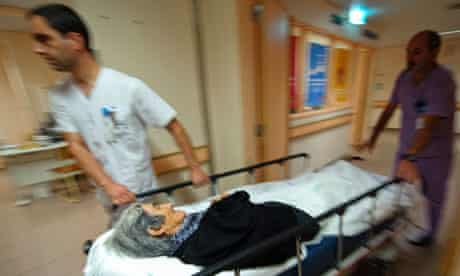 Healthcare professionals moving an old woman on a gurney in an hospital
