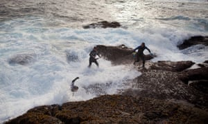 Percebeiros or barnacle fishers run from a wave while picking barnacles from the coast near Malpica de Bargantinos in Galicia, Spain. Traditional fishing is an important part of Galicia's economy. Barnacle fishers harvest when sea tide is low as waves recede from rocks so they can reach areas where the shellfish grow.
