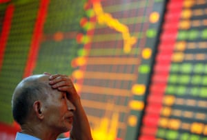 A stock investor reacts near a board displaying stock prices at a brokerage house in Huaibei in central China's Anhui province Monday June 24, 2013.