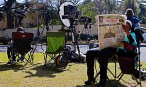 Members of the media wait outside the home of former South African President Nelson Mandela in Johannesburg, South Africa as he remains in a critical condition in hospital.