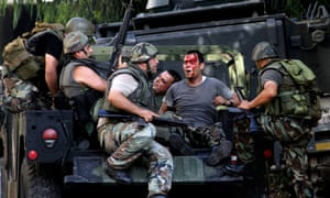 Lebanese army soldiers help injured soldiers after clashes between followers of a radical Sunni cleric Sheik Ahmad al-Assir and Shiite gunmen, in Sidon, Lebanon.