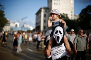 """A protester wearing a mask carries his daughter on his shoulders during a demonstration in central Sofia. Bulgaria's president said he would hold talks with all political parties on how to bring an end to protest rallies against graft and organised crime that have paralysed politics. The placard reads, """"We are not going to allow our children to live in a horror movie""""."""