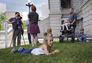 Coy Mathis, 6, lays in the grass at the Capitol as her mother Kathryn Mathis does a television interview in the background in Denver. Her father Jeremy and brother and sisters are also pictured. The Colorado Civil Rights Division has ruled in favor of six-year-old Coy Mathis, whose school had barred her from using the girls  bathroom at her elementary school because she is transgender.