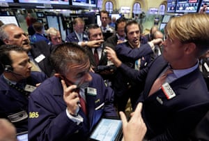 Traders gather at the post of specialist Patrick Murphy, right, on the floor of the New York Stock Exchange. Traders in the U.S. dumped stocks, bonds and commodities, prompted by signs of distress in China's economy and worries about the end of the Federal Reserve bank's easy money policies.