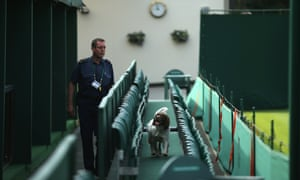 Police sniffer dogs sweep the grounds on day two of the Wimbledon Tennis Championships in London.