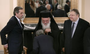 Greece's Prime Minister Antonis Samaras (L) and newly appointed Foreign Minister and Deputy Prime Minister Evangelos Venizelos (R) look at an official kissing the hand of leader of Greek Orthodox church Ieronimos (C) after a swearing in ceremony at the Presidential Palace in Athens June 25, 2013.