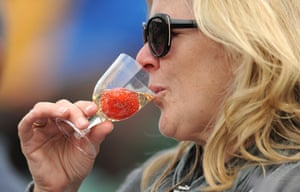 Fruity bouquet: A spectator drinks champagne with a strawberry at Wimbledon.