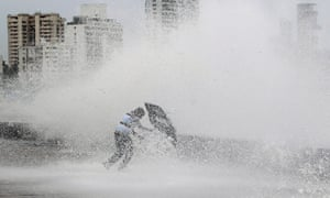 An Indian man struggles  pointlessly with his umbrella as waves lash the shore during a high tide in Mumbai, India.