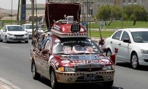 A Qatari decorates his car with images of Qatar's emir