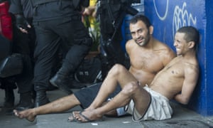 Two men arrested by security officers after gunbattles erupted in a slum in Rio de Janeiro, sit handcuffed on a pavement. Seven people, including one police officer, were shot dead during confrontations in a favela near Rio's international airport.