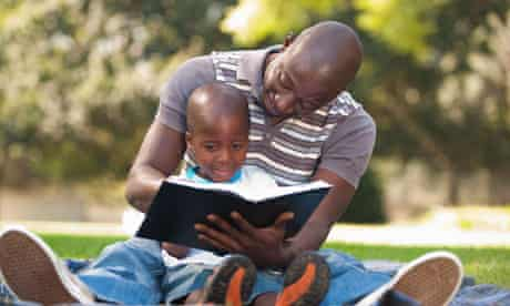 Father reading with son (4-5) on lawn, Johannesburg, Gauteng Province, South Africa