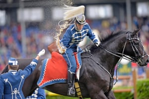 A Danish Guard hussar snatches a drink seated on a galloping horse during the opening ceremony of the CHIO Equestrian Festival in Aachen, Germany.