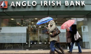 People walk past an Anglo Irish Bank bra