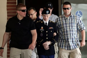 U.S. Army Private First Class Bradley Manning (C) is escorted from the courtroom after a day of his court martial trial at Fort Meade, Maryland.
