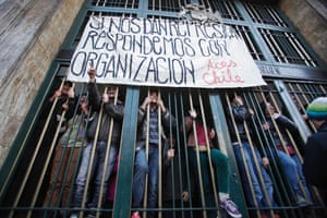 """Chilean high school students shout slogans from the Ministry of Education after they invaded the building and barred the doors in another protest against the government to demand changes in the public state education system in Santiago.  The banner reads, """"If they give us repression we will respond with organization."""""""
