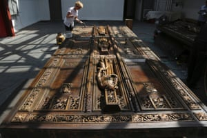 Lucia Popian, president of G&L Popian, applies polymeric micro crystalline wax while working on cleaning and restoring St. Patrick's cathedral's doors in New York. The bronze doors had been in place since the 1950s and hadn't been cleaned since. Photograph: Mary Altaffer/AP
