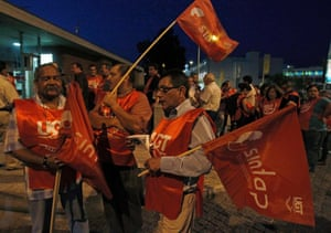 Workers hold flags at a picket line at the beginning of a general strike in Lisbon June 26, 2013.