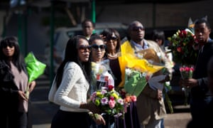 Relatives of Mandela carry bunches of flowers that were left by wellwishers. Photograph: Ben Curtis/AP