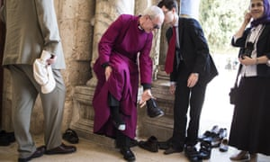 Archbishop of Canterbury Justin Welby takes off his shoes of before entering the mosque during his visit to the holy Muslim site the Al-Aqsa compound in Jerusalem. Reverend Welby is on a five-day tour of Egypt and the Holy Land.