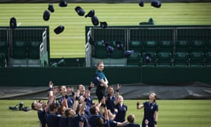 Ball boys and girls throw their hats in the air on day four of the Wimbledon Lawn Tennis Championships.