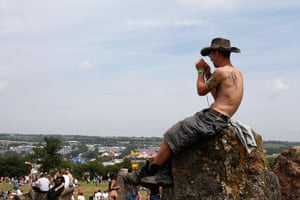 Glastonbury: A festival goer sits on top of one of the standing stones in the stone circ