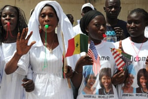 Senegalese women wearing tee-shirts with portraits of Senegal's First Lady Marieme Faye Sall and Michelle Obama stand at the roadside to welcome them before their visit to the Martin Luther King school in Dakar, Senegal.