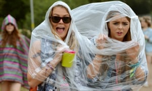 Festival goers sharing a poncho in the rain during the second day of the Glastonbury Festival.