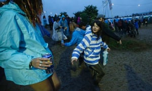 One festival goer offers to help another negotiate a muddy slope.