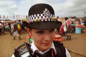 A policewoman wears a hat decorated with flowers.