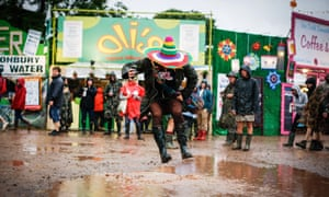 A festival goer makes a splash in a huge puddle.