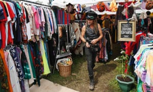 Bo, a mud sculptor, shops for clothes amongst vintage clothes stalls.