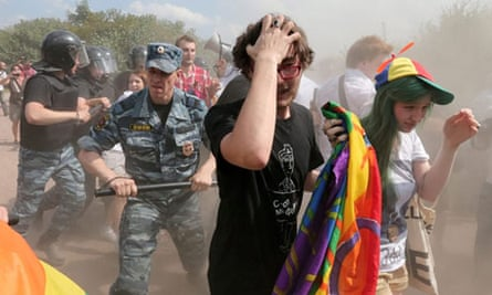 Police officers push a gay rights activist away from the scene of a Pride event in Saint Petersburg