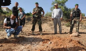 Lebanese soldiers inspect a site which was hit by a rocket, which residents say was recently fired from Syria overnight, in the town of Seriine in the Bekaa valley.