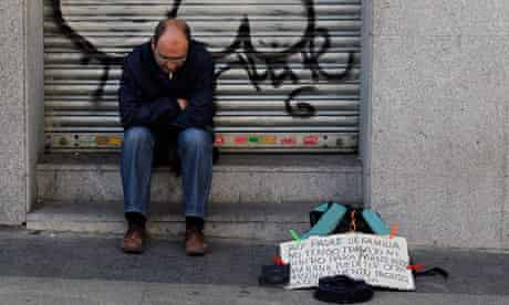 An unemployed Spanish man begs for money on a Madrid street