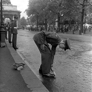 Queen's coronation 1953: A Royal Air Force man stoops as he gives his shoes a quick clean