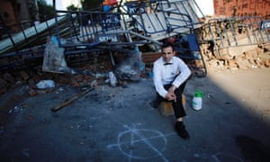 Seyfi Yasar, a waiter, pauses while smoking next to barricades outside a hotel near Taksim square in central Istanbul on 4 June. Pockets of protesters clashed with Turkish riot police overnight and a union federation began a two-day strike.