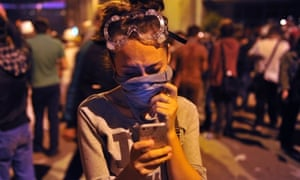 A female protestor uses mobile phone to report the latest news about the clashes near Taksim in Istanbul, Turkey, during a demonstration against the demolition of the park.